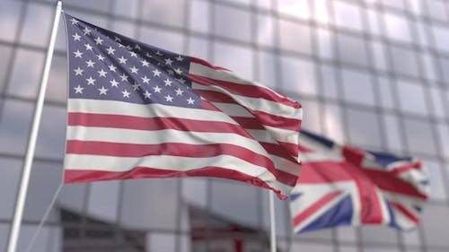 Waving Flags of the USA and the UK at Modern Skyscraper
