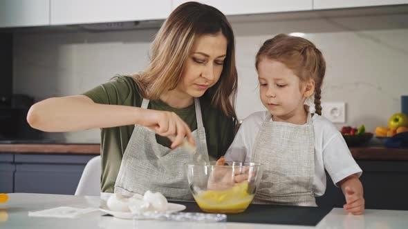 Mutter zeigt ihre kleine Tochter in der Küche