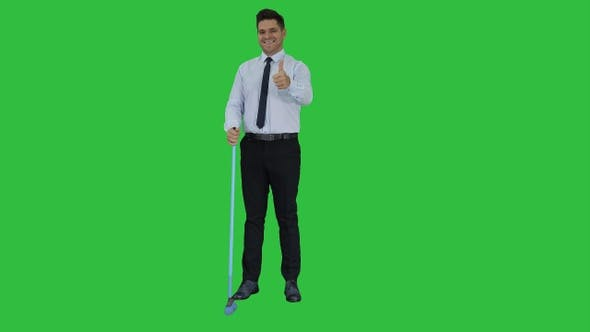 Thumbnail for Man with thumb up holding broom in formal clothes or business