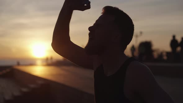 Tired Runner Is Pouring His Head By Water From Bottle After Jog in Evening