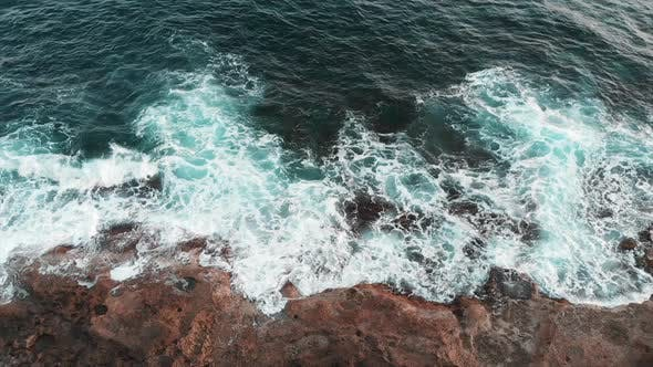 Top view of huge beautiful sea waves creating white foam and splashing during storm against rocks