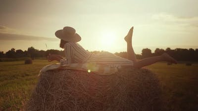 Beautiful girl in a dress lies on a haystack