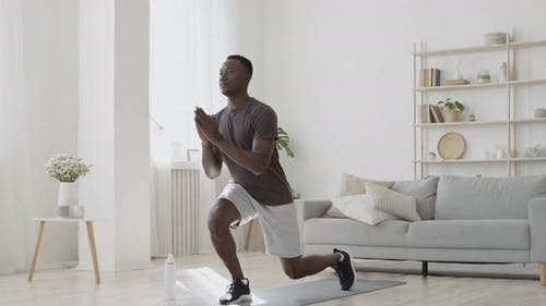 Athletischer Schwarzer Mann macht Vorwärtsausfallübungen zu Hause, trainiert Beine und Hüftmuskulatur