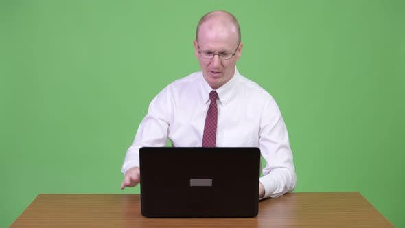 Thumbnail for Angry Mature Bald Businessman Talking To the Laptop Against Wooden Table