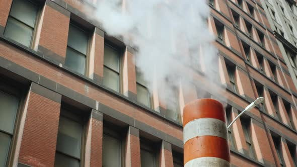 Cover Image for Steam Comes From the Striped Pipe, Against the Background of Tall Brick Buildings