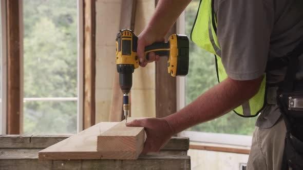 Thumbnail for Construction worker using cordless screw gun