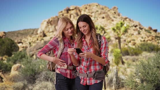 Thumbnail for Couple of pretty young female hikers taking selfies together in desert setting