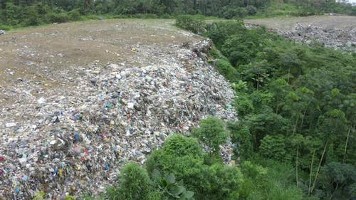 Aerial footage with a top down view of a garbage landfill in a tropical country