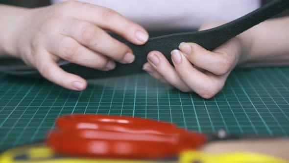 Skilled Tailor Checks Cut Leather Strip on Cushion Board