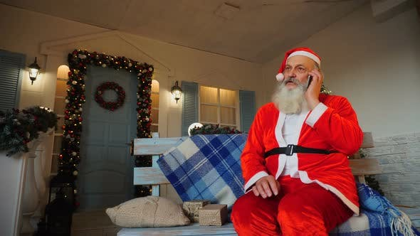 Thumbnail for Cheerful Father Christmas Congratulating on Holiday By Smartphone.