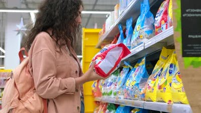 Female Student is Choosing Washing Powder in Supermarket