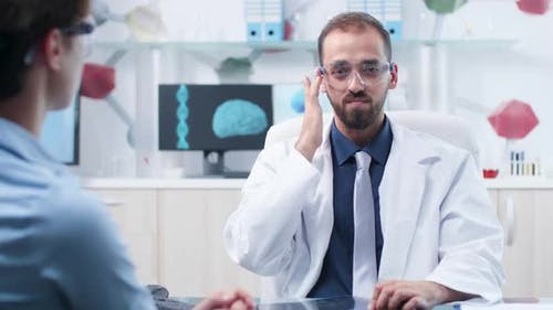 Caucasian Physician with AR Goggles Showing Something To a Patient