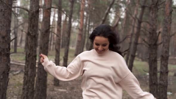 Thumbnail for Smiling young woman running through the forest