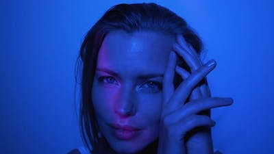 Model Doing Different Facial Poses in a Dark Room