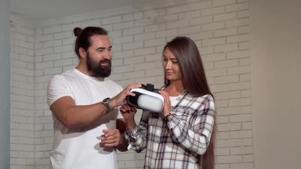 Cover Image for Handsome Bearded Man Watching His Girlfriend Using Virtual Reality Glasses