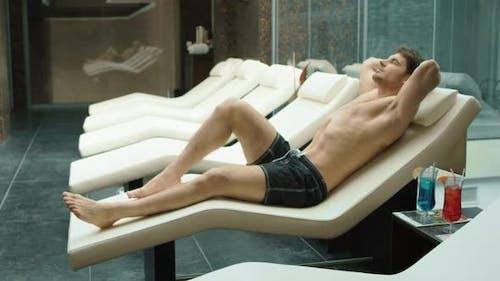Sportlicher Mann Entspannen im Wellness Resort. Sexy Guy Liegt auf Liege im Hotel Spa.