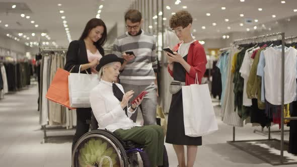 Thumbnail for Diverse Group of Friends Looking at Phone in Clothes Store