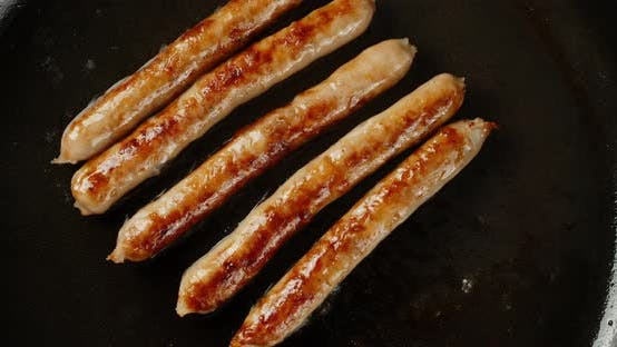 Thumbnail for Delicious Fried Sausage Slowly Rotates in a Frying Pan.
