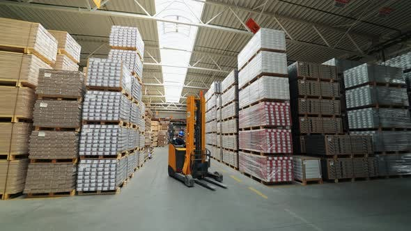 Thumbnail for An Electric Self Propelled Forklift Rides in Rows Between the Shelves with Parquet in the Stock
