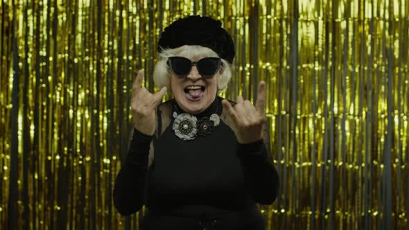 Thumbnail for Excited Positive Senior Woman Showing Rock and Roll Gesture and Sincerely Smiling, Showing Tongue