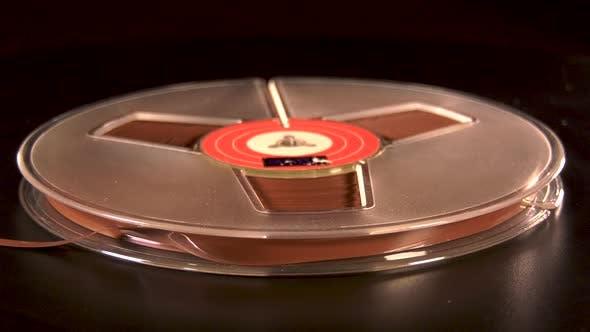 Reel to reel tape rotating before black background