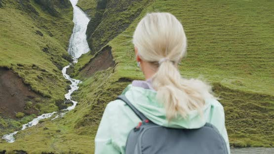 Woman Tourist with Backpack in Front of Icelandic Waterfall Near Fjadrargljufur at South Coast of