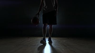 Basketball Player in Sportswear Red Shorts and a Blue T-shirt Goes on a Dark Basketball Court in the