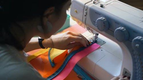 Seamstress Sews Fabric Strips with Sewing Machine Closeup