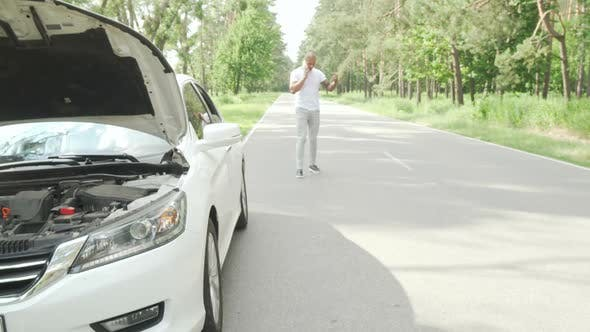Thumbnail for Man Calling Tow Truck Service on Countryside Road After His Car Broke Down