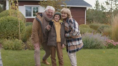 Aged Couple and Grandson Making Selfie Outdoors