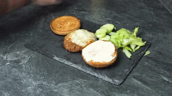 Thumbnail for Male Hand in Tattoos Spreading Cream Cheese on a Sandwich and Putting Lettuce, Cucumber and Meat