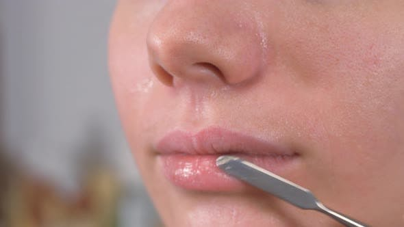 Thumbnail for Preparing the Model's Skin for Applying Makeup. Lip Treatment with a Spatula and Lip Balm. Close Up.