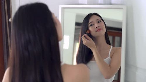 Beauty portrait asian woman applying makeup with brush of cheek look at mirror indoors.
