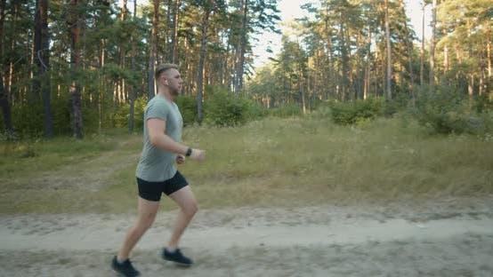 Thumbnail for Muskulärer Mann in Sportbekleidung Joggen im Wald