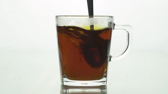 Spoon Stirs Tea in Transparent Glass Cup Creating Whirl, Sugar Particles Spinning Brewing Tea. Slow