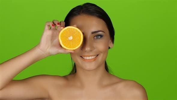Thumbnail for Mädchen schließt orange Augen, lächelt und entfernt Orange. Grüner Bildschirm