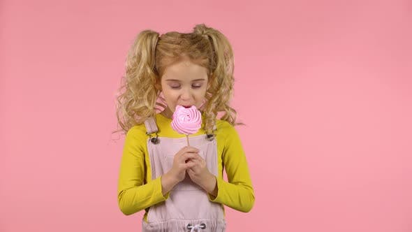 Pretty Female Child Is Eating a Candy on the Stick