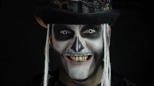 Creepy Man Face in Skeleton Halloween Cosplay Appearing on Black Background. Making Faces, Smiling