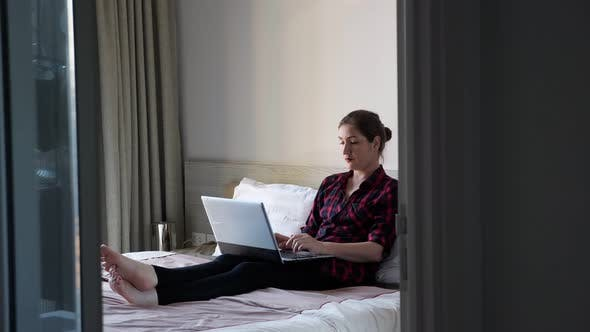 Lady Sits on White Bed and Types on Grey Modern Laptop