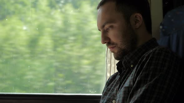 Businessman Commuting On Train Using Digital Tablet.