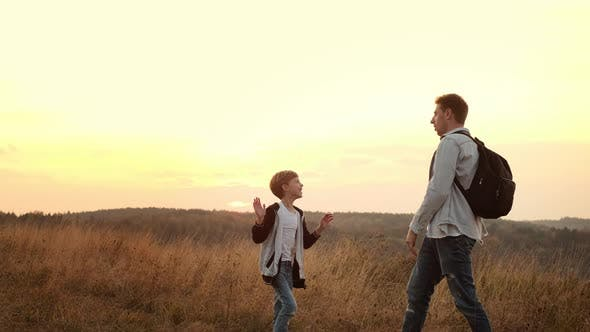 Walk In The Nature Of Dad And Son. Dad And Little Son Greet Each Other Clapping Their Hands.