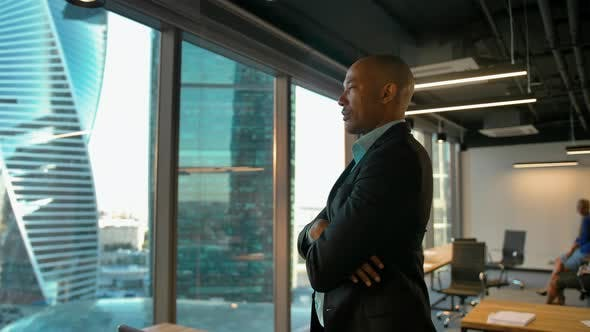 Aframerican Entrepreneur Standing Near Huge Modern Office Window with Serious Expression