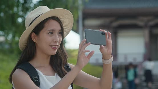Thumbnail for Woman travel in Japan, take photo on mobile phone in the Japanese temple