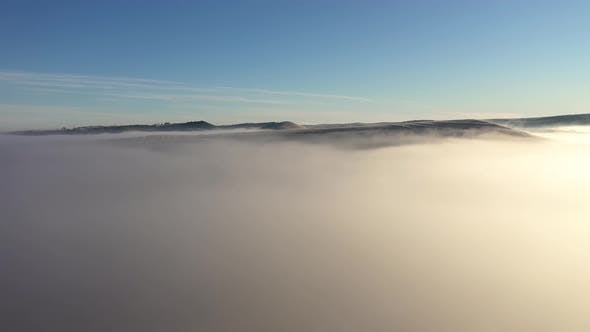 Misty View of Drone Raising Above the Clouds. Aerial Shot