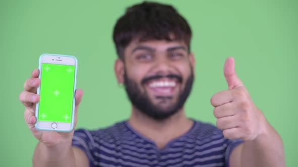 Thumbnail for Face of Happy Young Overweight Bearded Indian Man Showing Phone and Giving Thumbs Up