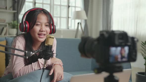 Asian Girl Vlogger Singing While Streaming. The Child Is Broadcasting Live On The Internet