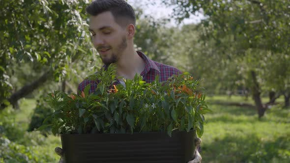 Thumbnail for Portrait of Young Smiling Bearded Farmer Holding a Pot of Flowers in Hands Walking