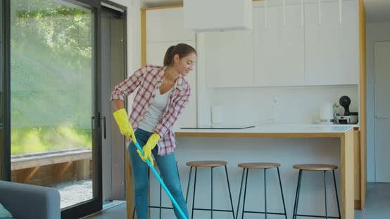 Thumbnail for Attractive Girl Is Mopping Floor at Home and Having Fun. Women, Joy and Houses Concept.