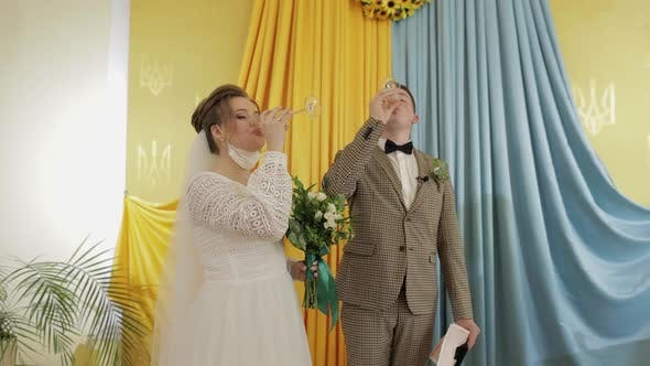 Newlyweds. Caucasian Groom with Bride Drink Champagne and Make a Kiss on Ceremony. Wedding Couple