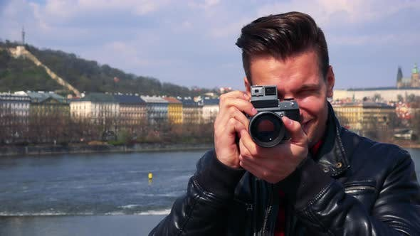 Thumbnail for A Young Handsome Man Takes a Photo of the Camera with His Own Camera and Smiles - Closeup